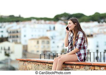 Happy teen talking on phone sitting on a ledge