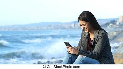 Happy teen texting on phone on the beach - Happy teenage...