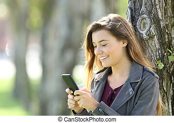 Happy teen using a smart phone outdoors