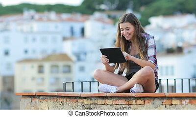 Happy teen using a tablet on vacation