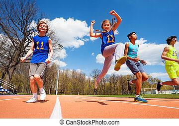 Happy teenage athletes running in the stadium