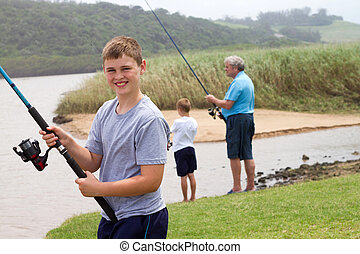 teenage boy fishing with grandpa and little brother