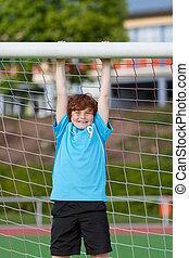 teenage boy hanging on soccer goal