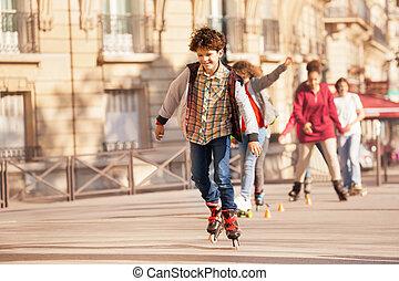 Happy teenage boy roller skating at city side walk