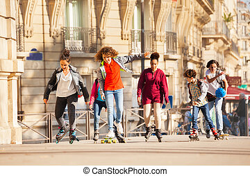 Happy teenage boys and girls rollerblading in city