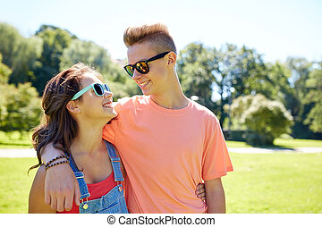 happy teenage couple looking at each other in park