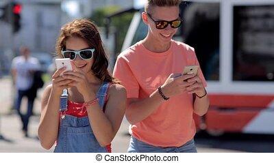 happy teenage couple with smartphones in city - summer...