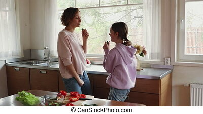 Happy teenage daughter and mom enjoying singing and cooking