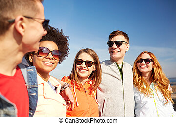 happy teenage friends in shades talking on street - tourism,...