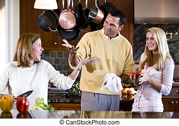 Happy teenage girl and parents chatting in kitchen