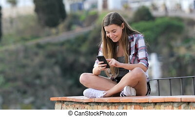 Happy teenage girl browsing phone content on a ledge