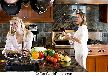 Happy teenage girl in kitchen with mother