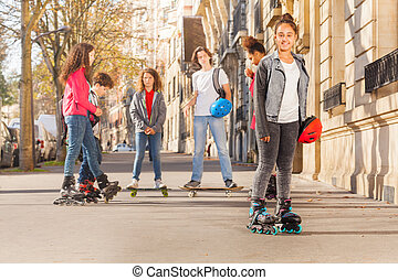 Happy teenage girl in roller skates with friends