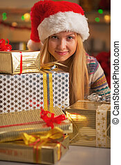 Happy teenage girl in santa hat with stack of christmas present boxes