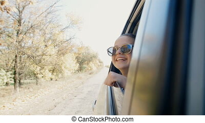 Happy teenage girl in sunglasses rides in the car and stuck...