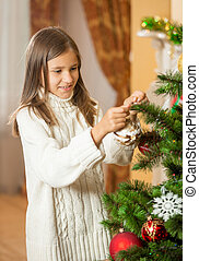 Happy teenage girl in woolen sweater decorating Christmas tree at house