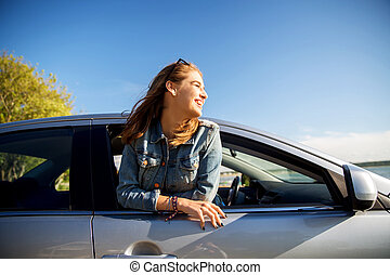 happy teenage girl or young woman in car - summer vacation,...