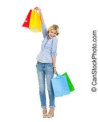 Happy teenage girl rising up shopping bags