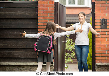 Happy teenage girl running to her mother after going from school