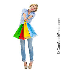 Happy teenage girl showing shopping bags