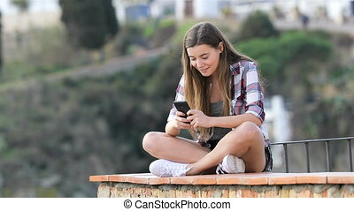 Happy teenage girl texting on phone in a town