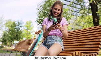 happy teenage girl with smartphone and longboard -...