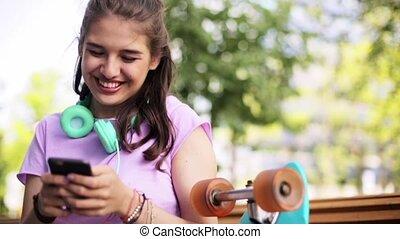 happy teenage girl with smartphone and longboard