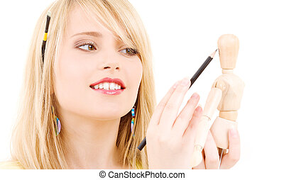 happy teenage girl with wooden model dummy over white
