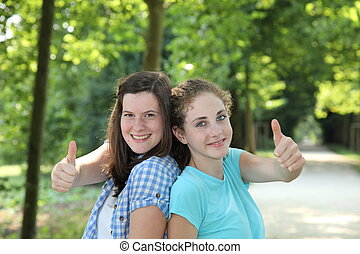 Happy teenage girls giving a thumbs up - Happy attractive...