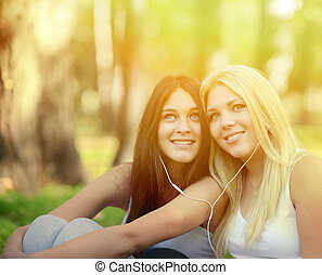 Happy teenage girls listening to music outdoors