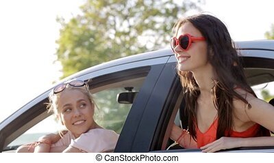 happy teenage girls or women in car at seaside 10