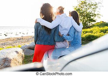 happy teenage girls or women near car at seaside