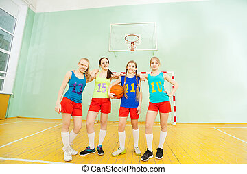 Happy teenage girls posing with basketball in gym