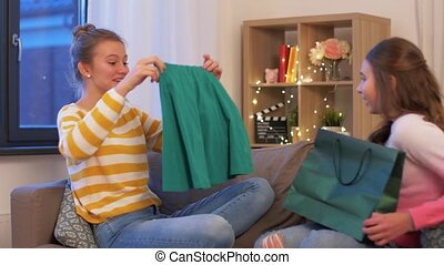 happy teenage girls with shopping bags at home - people, ...