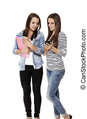 happy teenage students looking at a smartphone on white background