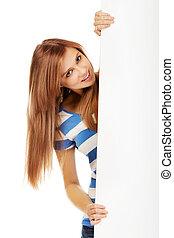 Happy teenage woman holding blank banner