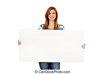 Happy teenage woman with blank billboard