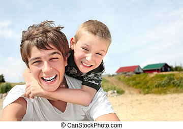 happy teenager and kid on the beach