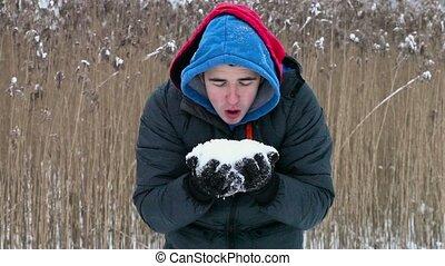 Happy teenager blowing snow