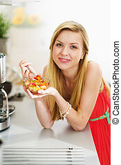 Happy teenager girl eating fresh fruits salad in kitchen