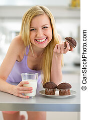 Happy teenager girl eating muffin with milk in kitchen