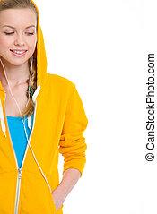 Happy teenager girl in earphones looking on copy space