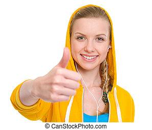 Happy teenager girl in earphones showing thumbs up