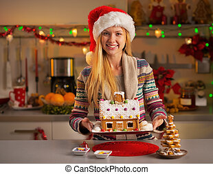 Happy teenager girl in santa hat showing christmas cookie house