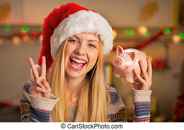 Happy teenager girl in santa hat showing victory gesture and pig