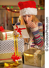 Happy teenager girl in santa hat with stack of christmas present