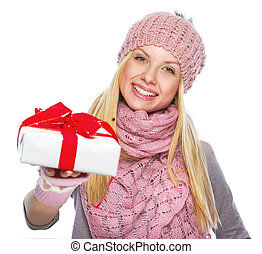 Happy teenager girl in winter hat and scarf giving presenting box