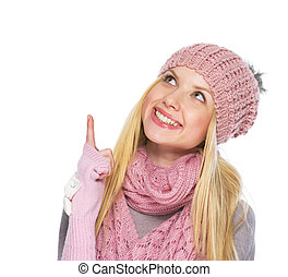 Happy teenager girl in winter hat and scarf pointing up on copy space