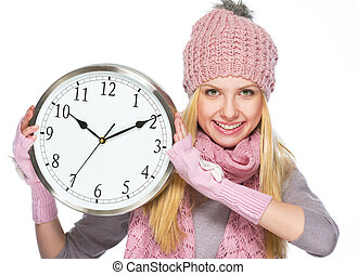 Happy teenager girl in winter hat and scarf showing clock