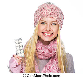Happy teenager girl in winter hat and scarf showing pills pack